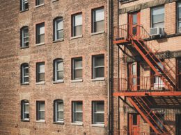 brick building with windows and red fire escape