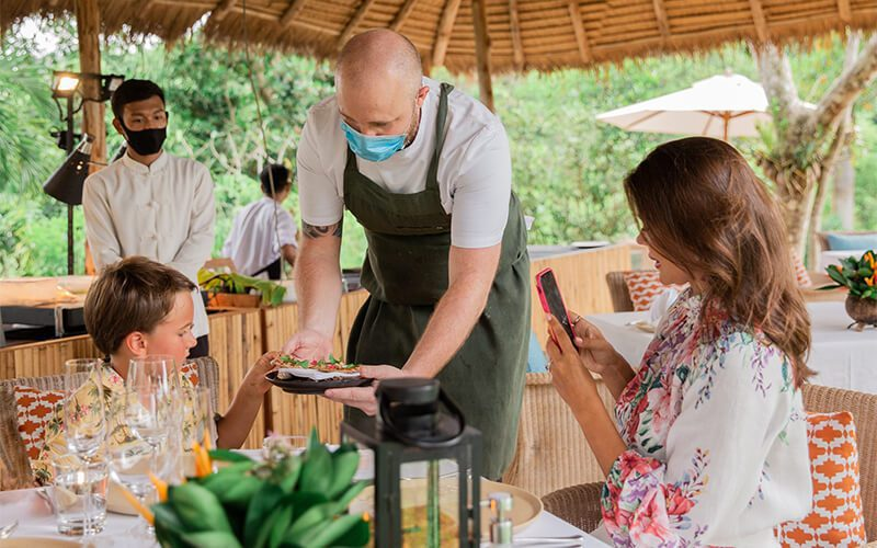 waiter serving a guest at the Trisara Hotel in Thailand
