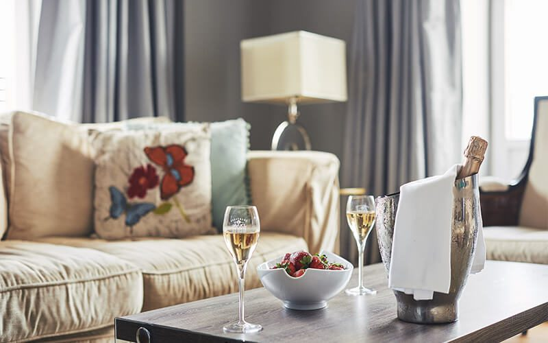 champagne and strawberries on a table in a hotel room