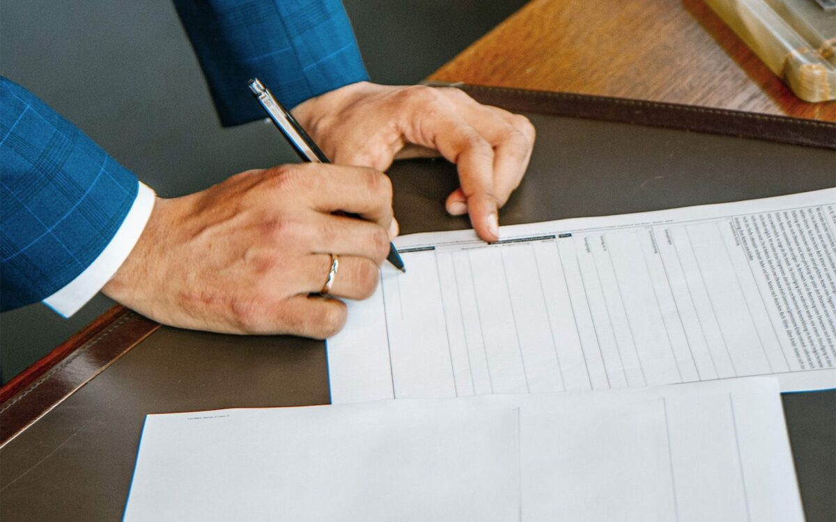 Person signing a blank contract form