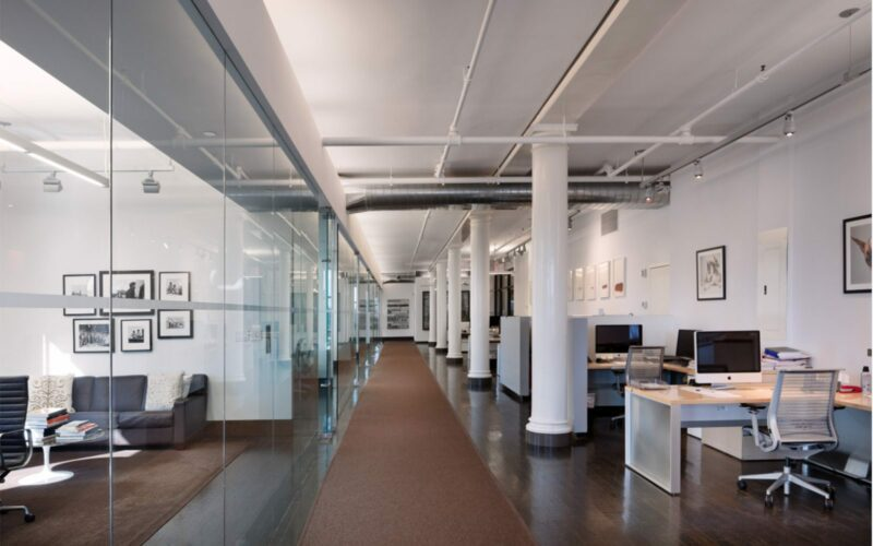 Office space inside a building in New York including desks, computers, and rooms with glass doors.