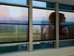 A woman reflected in the window of a commercial property