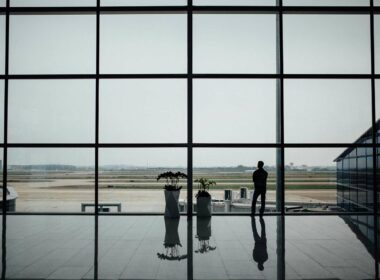 A man looks out the window of a lonely airport.