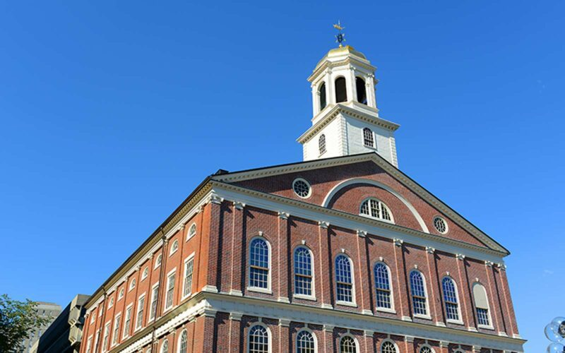 Boston's Faneuil Hall sits against a blue sky.