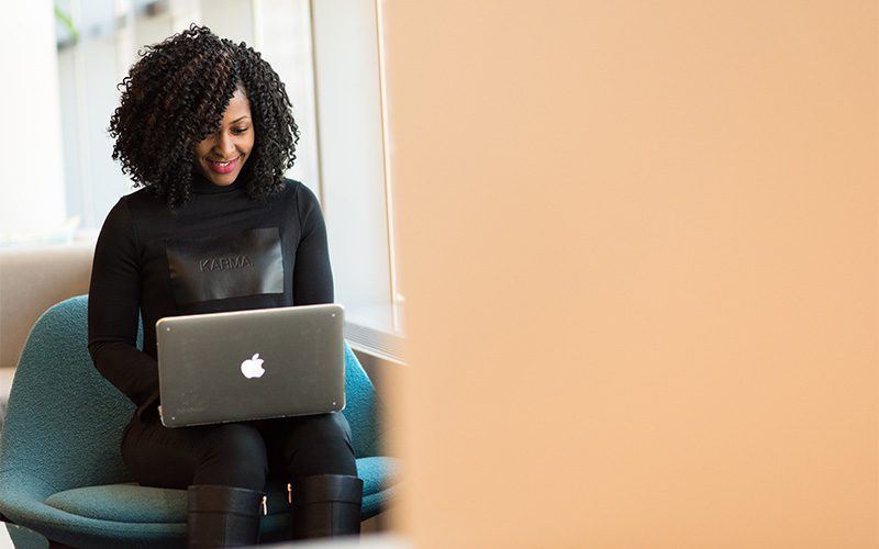 An investor manages her portfolio on a laptop.