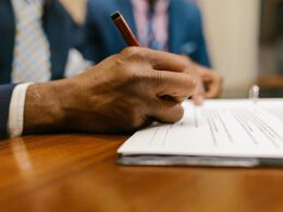 Documents are signed in pen.