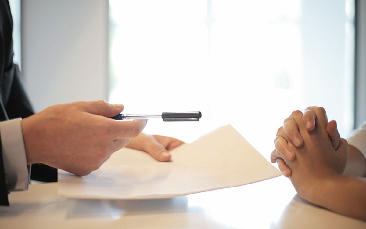 Paperwork is discussed in an office.